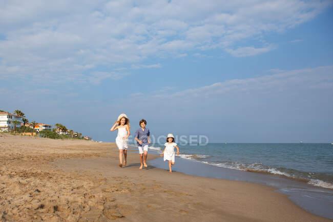 Счастливые и улыбающиеся дети в повседневной одежде бегают босиком по берегу моря на песчаном пляже в летний солнечный день — стоковое фото