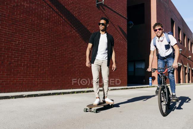 Jeunes hommes afro-américains à vélo et planche à roulettes — Photo de stock