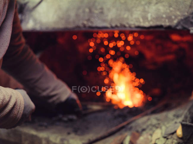 Руки ковальського вручає в рукавичках з розплавленого металу молотком по стародавніх ковадів в традиційному семінарі — стокове фото