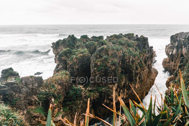 Paisagem do mar tempesante que flui nas rochas no dia nebuloso — Fotografia de Stock