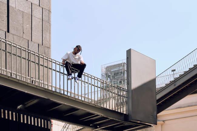 Молодий афроамериканець чоловік, сидячи на перил мосту на міській вулиці в сонячний день — стокове фото