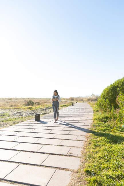 Босоніж дівчина в повсякденний одяг і читання гарною книгою під час прогулянки по пиломатеріалів шлях в природі — стокове фото