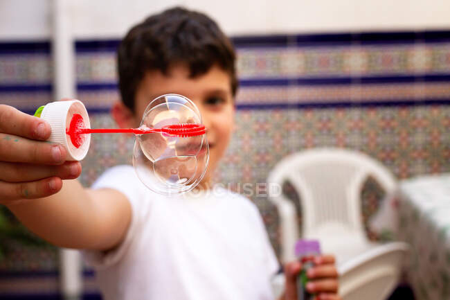 Little boy in white T-shirt playing soap bubbles while standing on terrace at home — Stock Photo