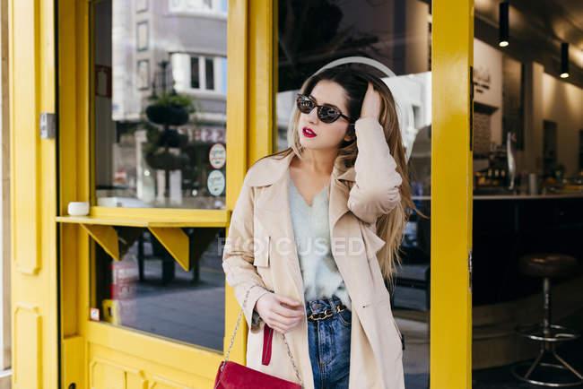 Молода Чуттєва жінка в стильному спорядження і сонцезахисні окуляри стояв біля кафе і дивиться — стокове фото