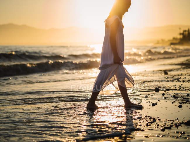 Маленькая девочка в белом платье гуляющая по берегу моря на фоне заката — стоковое фото