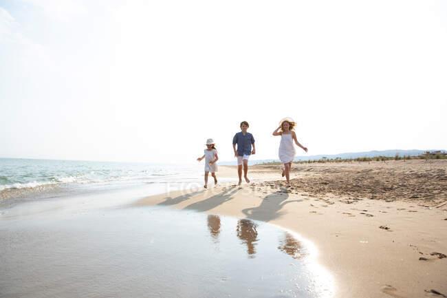 Crianças felizes e sorridentes em uso casual correndo descalço ao longo da costa na praia de areia no dia ensolarado de verão — Fotografia de Stock