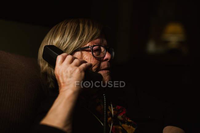 Belle femme âgée souriante qui répond à un appel téléphonique dans une pièce sombre le soir à la maison — Photo de stock