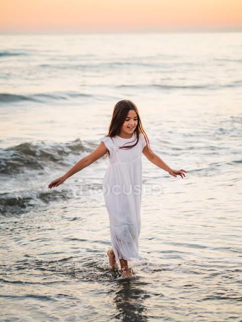 Маленькая девочка в белом платье гуляющая и играющая на берегу моря на фоне заката — стоковое фото
