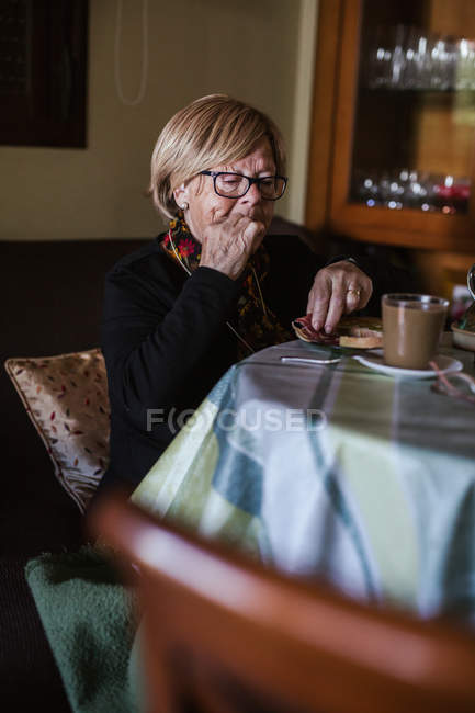 From above aged woman having breakfast while sitting at table — Stock Photo