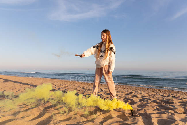 Cheerful female teenager in casual outfit smiling and holding colored smoke signal while standing on sandy shore near waving sea — Foto stock