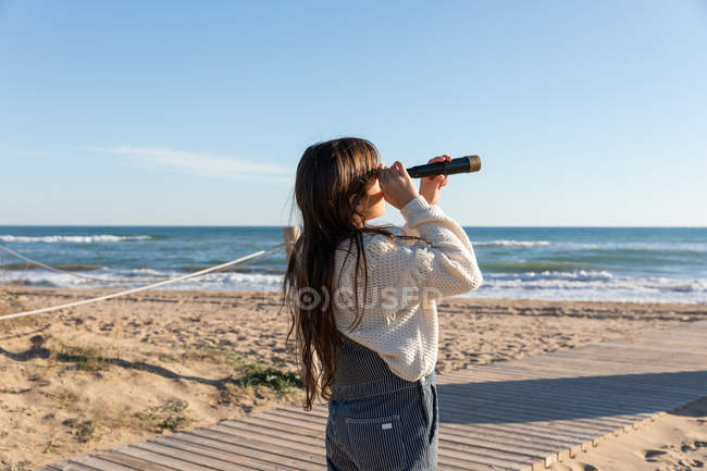 Girl in casual outfit using spyglass to look at distance while standing on beach near waving sea — Stockfoto