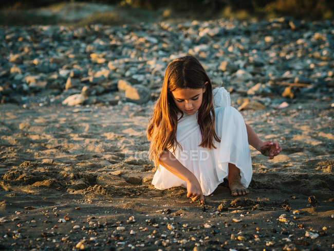 Cute pensive female kid in white dress playing with sand on seaside in sunlight — Stock Photo