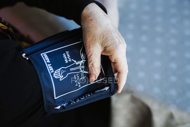 Abgeschnittenes Bild einer Frau mit Tensiometer zur Messung des Blutdrucks, während sie zu Hause am Tisch sitzt — Stockfoto