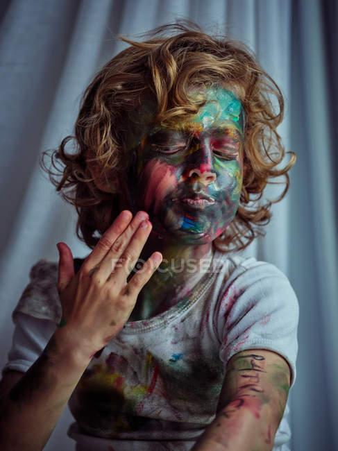 Кумедний хлопчик, пофарбований у яскраві фарби, сидить біля штор і малює в собі барвистий живопис. — стокове фото