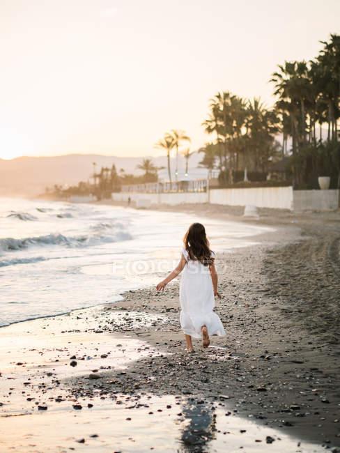 Petite fille en robe blanche marchant sur le bord de la mer sur fond de coucher de soleil — Photo de stock