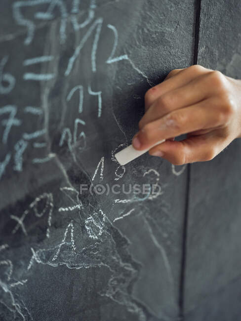 Crop hand of unrecognizable child writing by chalk multiplication table on grey stone wall — Stock Photo