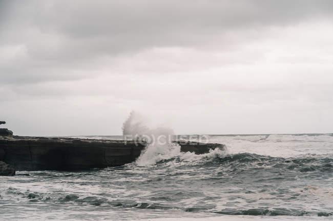 Água do mar tempestuoso acenando perto de penhasco rochoso contra o céu nublado cinza — Fotografia de Stock