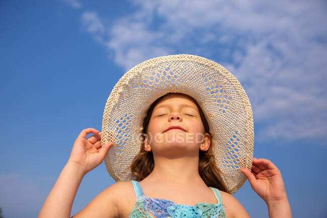 From below cute girl in blue knitted dress and wide-brimmed hat standing in summer day — Stock Photo