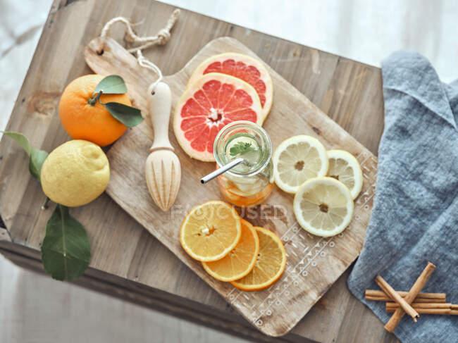 Сверху композиция лимонов, грейпфрута и апельсинового лимонада в стеклянной бутылке в деревянной доске — стоковое фото