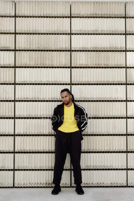 Joven afroamericano en ropa deportiva de moda mirando a la cámara mientras está de pie cerca de bloques de cemento en la calle de la ciudad - foto de stock