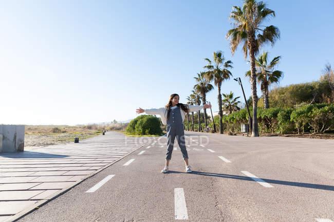 Дівчина стояла на Близькому асфальті дороги на приміській вулиці біля пальм в сонячний день — стокове фото