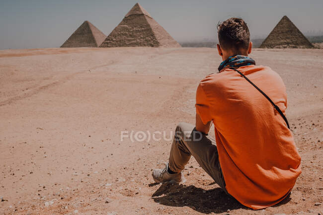 Впевнений чоловік - мандрівник сидить у пустелі проти відомих великих пірамід у Каїрі (Єгипет). — стокове фото
