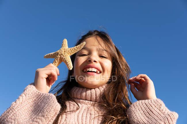 Симпатичні Веселі дівчата в светри зворушливі волосся і демонстрації морськими зірками, стоячи проти безхмарне небо — стокове фото