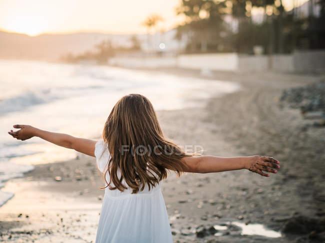 Cheerful cute female child in white dress having fun on sandy seashore at sunset — Stock Photo