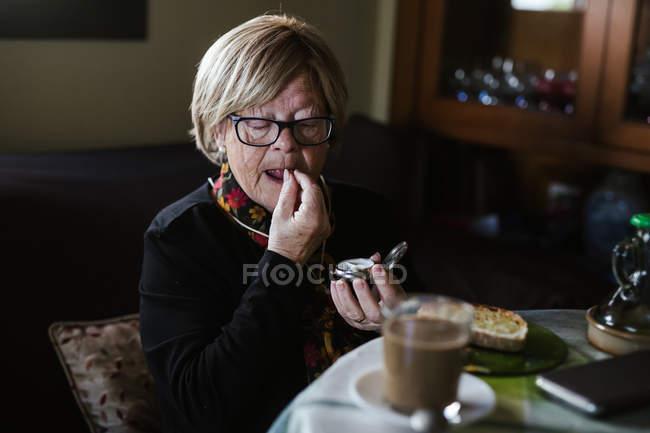 Mujer atractiva mayor que toma medicamentos de la caja de pastillas antes del desayuno - foto de stock