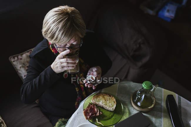 Старшая привлекательная женщина принимает лекарства из коробки с таблетками перед завтраком — стоковое фото