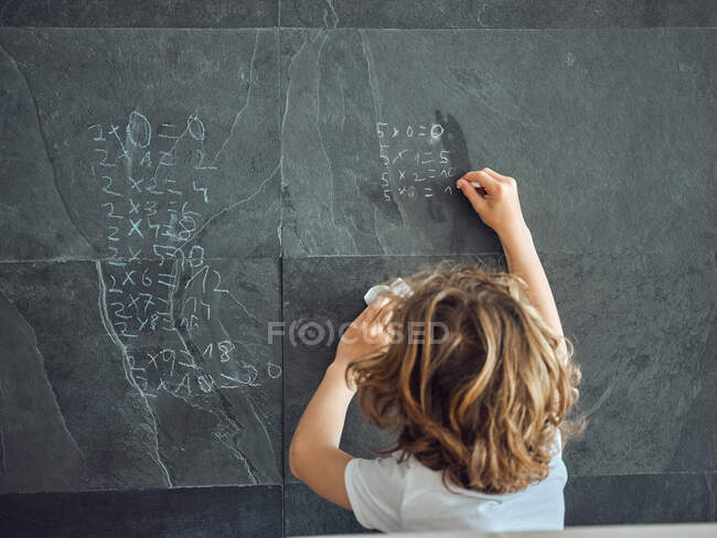 Back view of long hair boy writing by chalk multiplication table on grey stone wall — Stock Photo