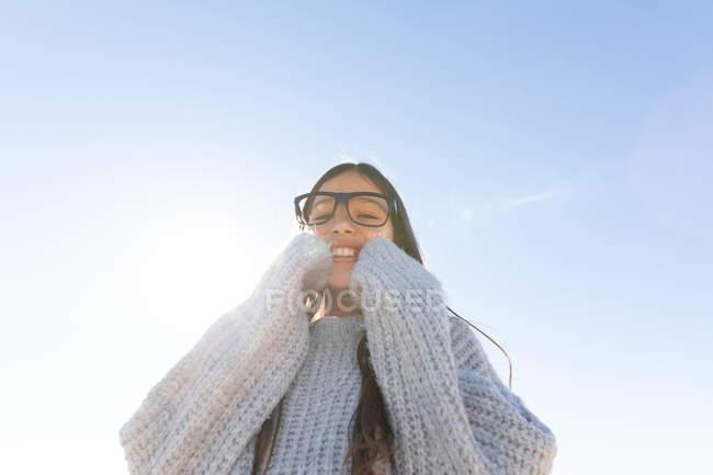 Весела дівчинка в трикотажної светри і окуляри посміхаються і дивляться на камеру проти безхмарне Синє небо з яскравим сонцем — стокове фото