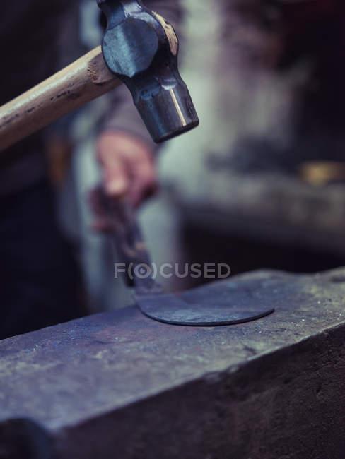 Крупний план ковальського кування металу з молотком по старій ковадлі в традиційному семінарі — стокове фото