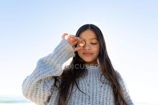 Симпатичні дівчата в светр проведення морських зірок перед очима, стоячи проти безхмарне небо — стокове фото