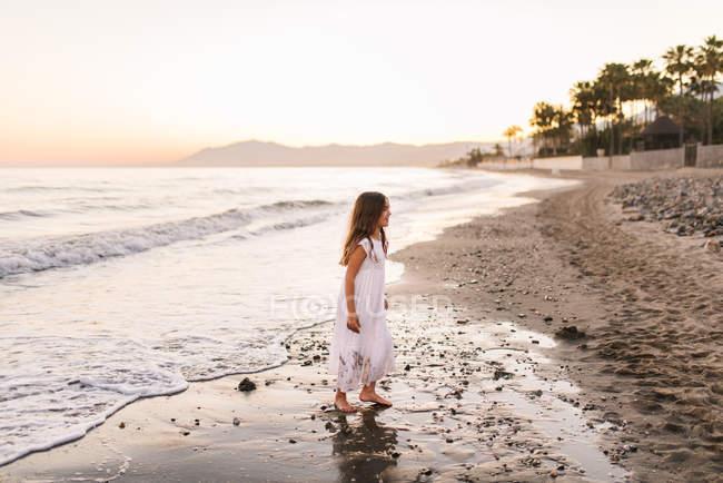 Allegro carino bambino femminile in abito bianco divertirsi sulla spiaggia sabbiosa al tramonto — Foto stock