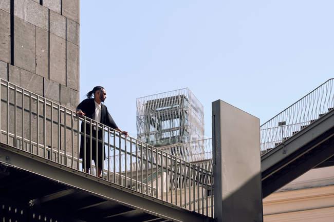 Молодий афроамериканець чоловік, спираючись на перила мосту на міській вулиці в сонячний день — стокове фото