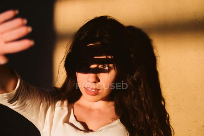 Молодая женщина в повседневной одежде загораживает солнце рукой и улыбается у стены — стоковое фото