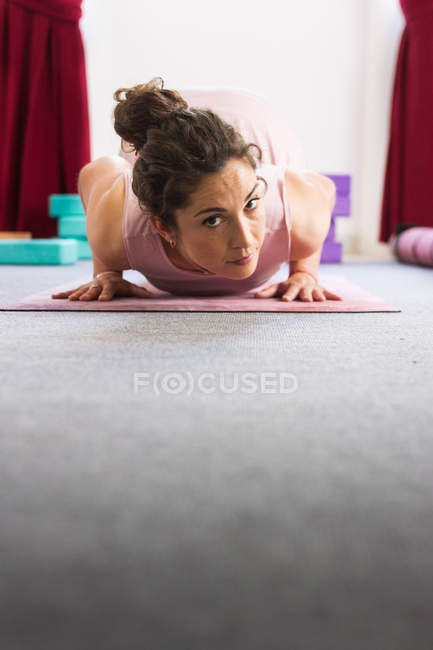 Flexible sportive concentrated brunette in sportswear doing lying yoga pose on mat — Stock Photo
