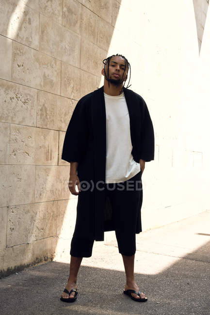 Young African American male in stylish outfit looking at camera while standing near grungy wall on sunny day on city street — Stock Photo