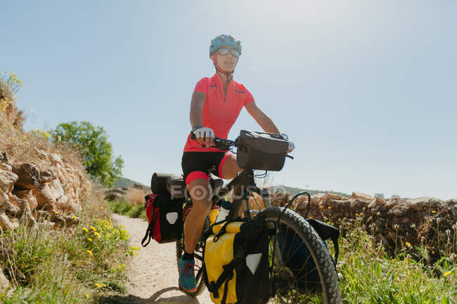 Lady in sportswear and helmet riding bike on stony path while traveling through forest on sunny day in countryside — Stock Photo