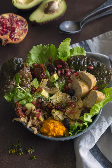 Bowl of delicious lettuce and avocado salad with pieces of bread and pomegranate seeds placed near napkin — Stock Photo