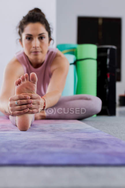Young athletic brunette practicing yoga pose while sitting on mat in studio — Stock Photo