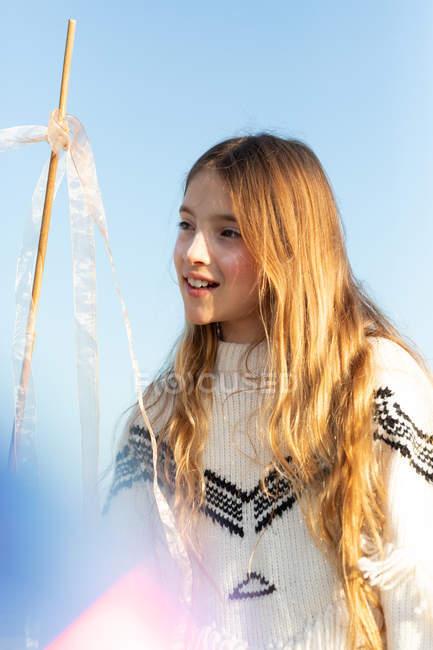 Веселий жіночий підліток у стильному кофті тримає палицю з стрічками і дивиться геть проти безхмарне Синє небо — стокове фото