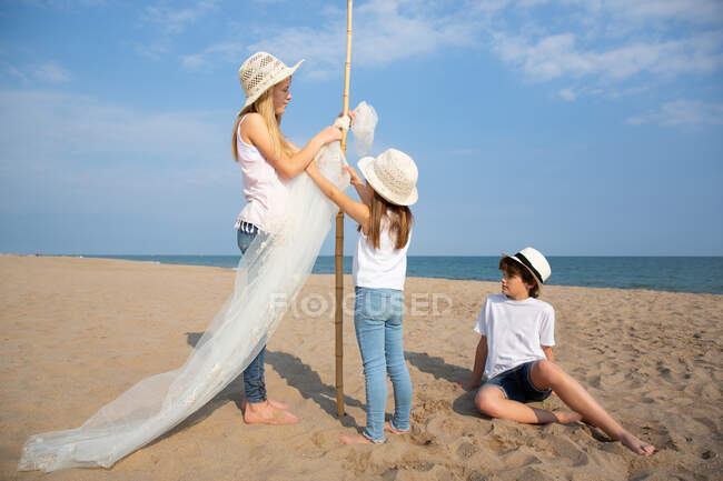 Girls in hats attaching awning on pole while boy sitting on sand on beach — Stock Photo