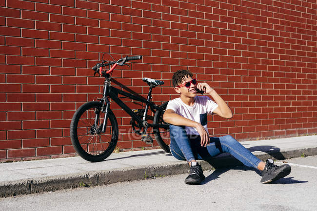 Young happy black man talking smartphone on bike — Stock Photo