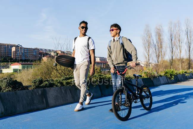 Молодые черные счастливые друзья мужского пола, гуляющие по городу — стоковое фото