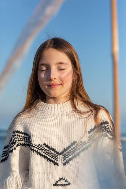 Симпатичні підлітка з закритими очима стоячи на пляжі — стокове фото