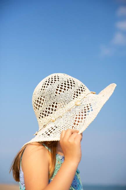 Da sotto ragazza carina in abito blu a maglia e cappello a tesa larga in piedi in giorno d'estate — Foto stock