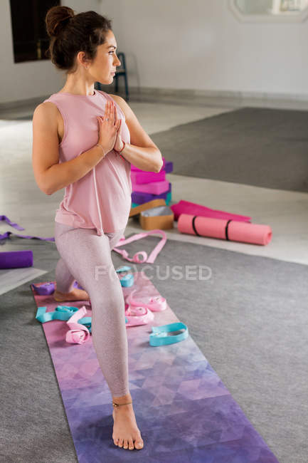 Slim brunette in comfortable sportswear holding hands in namaste position while practicing yoga in studio — Stock Photo