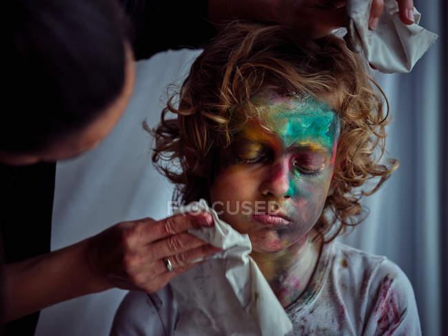 Жінка з серветками, що прибирають творчого хлопця з білявим волоссям, намазаним барвистими фарбами. — стокове фото